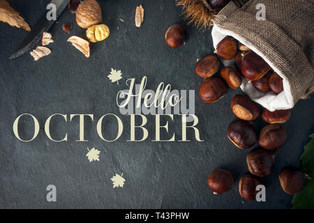 Hello october card. Roasted chestnuts on a rock table with a knife. - Stock Image