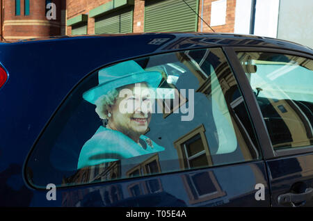 Picture of Her Majesty the Queen on the rear offside window of a small family car - Stock Image