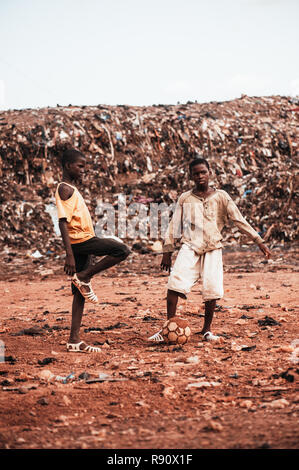 Mali, Africa - Black african children playing soccer with caucasian volunteer in a rubbish dump. Rural area near Bamako - Stock Image