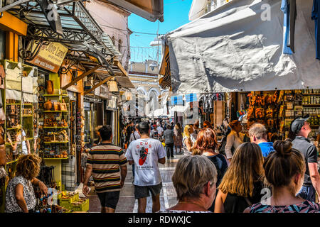 Athens, Greece - September 22 2018: Tourists walk the streets lined with souvenir shops and cafes in the touristic Plaka section of Athens, Greece - Stock Image