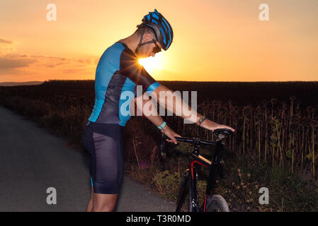 Man standing in sunset lights on an empty road and holding a bicycle . - Stock Image