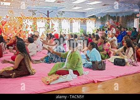 A Hindu congregation of mostly women extend their arms and wave during prayer services in Jamaica, Queens, New York City. - Stock Image