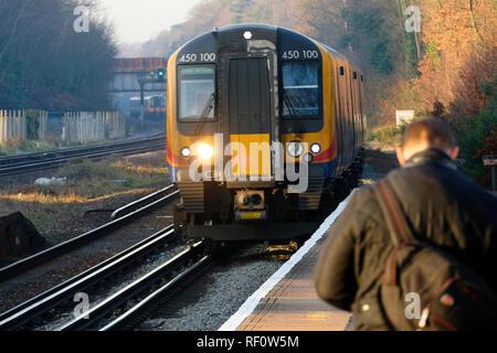 British Passenger train approaching railway platform, London, United Kingdom. - Stock Image