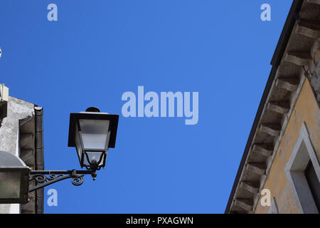 decorative and nostalgic street lamp in front of azure sky, vintage iron street lantern on a house facade - Stock Image