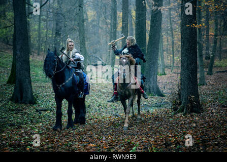 Warriors Woman an Man on horses in the woods. Scandinavian vikings riding horse with axes in hands. Traditional clothes with fur collar. Reconstructio - Stock Image