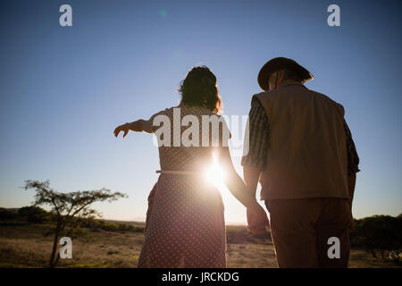 Couple pointing at distance during safari vacation - Stock Image