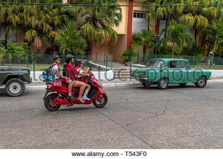 Three people riding on an E-bike which are known in the island as 'motorina' . The unsafe practice has become common in the island and transit police  - Stock Image