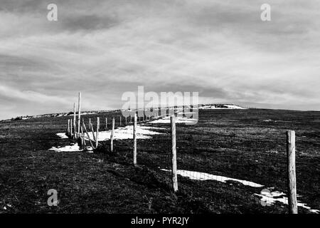 Wooden fence posts and barbed wire marking the property line of a prairie with dried grass and patches of snow under moody sky - Stock Image