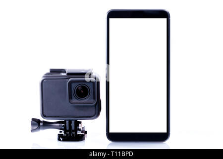 A modern video sports camera next to a black smartphone with screen in blank isolated on white. - Stock Image