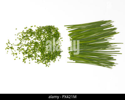 chopped and whole chives on a white background - Stock Image