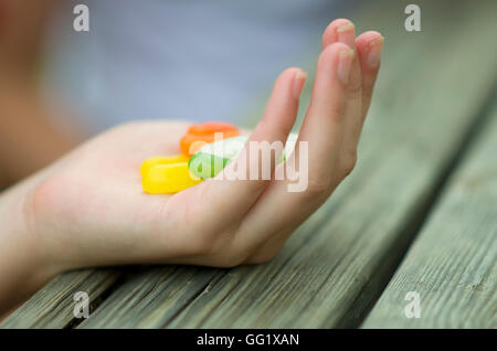 Colourful jelly beans in a cupped hand. - Stock Image