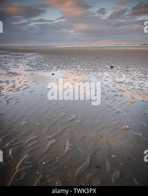 sunset clouds reflecting on wet sands at the beach - Stock Image