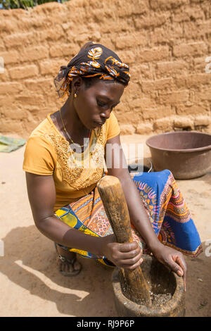 Kisambo Village, Yako, Burkina Faso, 28th November 2016;  Miriam Ouedraogo,, cooking a meal for 10, grinding herbs to go with moringa leaves just picked from the village garden. - Stock Image