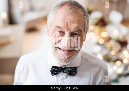 A close-up portrait of a senior man standing indoors in a room set for a party. - Stock Image