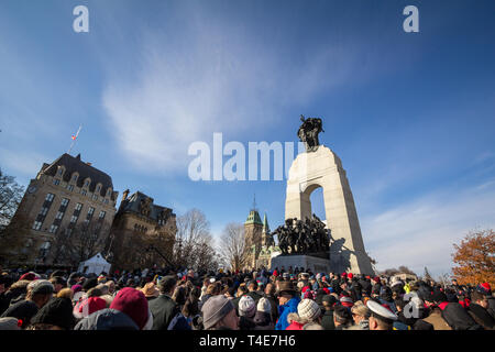 OTTAWA, CANADA - NOVEMBER 11, 2018: Crowd gathering on National War memorial, with parliament in background, on remembrance day to commemorate the can - Stock Image