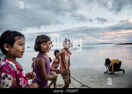 Children play on San Hlan beach in southern Myanmar. - Stock Image