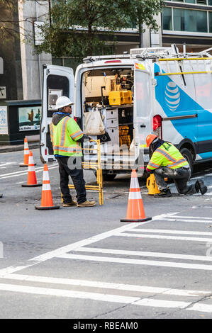 CHARLOTTE, NC, USA-1/8/19: Two utility workers at back of open work van in city street in uptown. - Stock Image