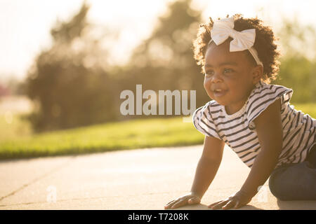 Happy African American little girl laughing and smiling outside. - Stock Image