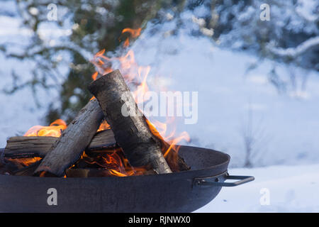Firepit in the snow with log fire - Stock Image