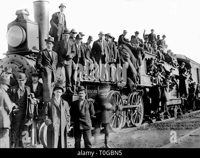 A crowd of men gathers on and around a Chicago, Milwaukee,  & St. Paul locomotive in Ladd, Illinois in 1909. - Stock Image