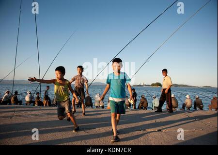 Les enfants sont toujours au rendez-vous lorsque les pêcheurs viennent en fin d'après midi le long - Stock Image