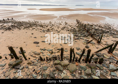 Decayed old groynes on the beach at Llanfairfechan, North Wales - Stock Image