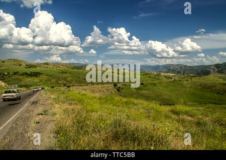 A turn on the road leading to a mountain village located high in the mountains of the Gegham mountain range against a blue sky covered with cumulus in - Stock Image