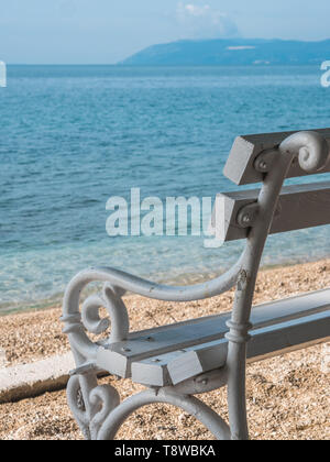 Wooden bench near the sea on sunny day close up - Stock Image