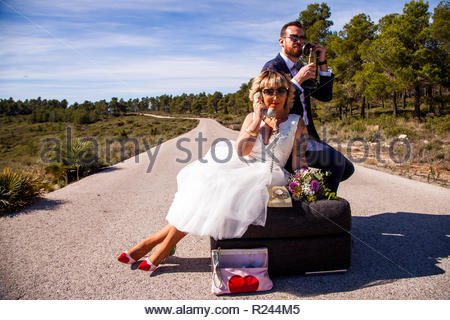 Newlywed couple pose on their sofa in the middle of a lonely road with vintage phones - Stock Image