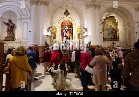 People in a chapel, interior of the Iglesia de Santiago (Church of Santiago), the oldest Roman Catholic church in Malaga, Andalucia, Spain Europe - Stock Image