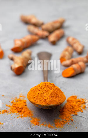 turmeric powder in an old vintage spoon, turmeric roots on a gray concrete background - Stock Image