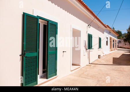 Whitewashed Portuguese farmhouse cottage with red terracotta roof tiles in rural Algarve, Portugal. - Stock Image