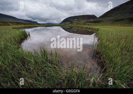 Reflection of mountain landscape of Tjäktjavagge valley in small pond near Sälka hut; Kungsleden trail; - Stock Image