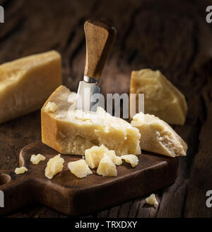 Piece of Parmesan cheese and cheese knife on the wooden board. Dark background. - Stock Image