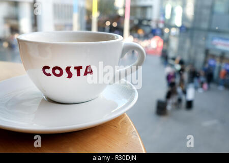 A cup of Costa coffee in a large Costa cup clearly showing the company logo across the cup. in a coffee shop with a busy city in the background - Stock Image