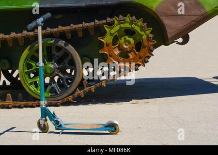 Kids' scooter in front of a part of a caterpillar track on a military amphibious vehicle. The vehicle has a verdant camouflage scheme on it. - Stock Image