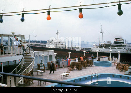 1960s, cruise ship in a port, people on the deck showing deckchairs stacked up and empty swimming pool. - Stock Image