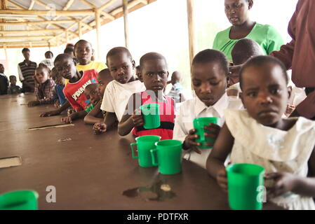 a long queue of African children line up in smart clothes, holding plastic mugs and plates waiting for food in East Africa - Stock Image