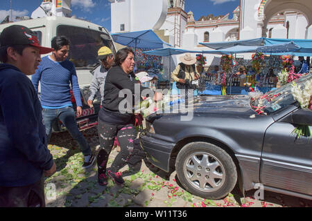 Pouring champagne on one's car after it has been blessed, a unique ritual at the Basílica de Nuestra Señora in Copacabana, Bolivia - Stock Image