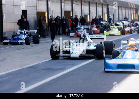 Historic Formula 1, 2 and 3 racing cars assemble in the International Pit Lane, for a parade lap, during the 2019 Silverstone Classic Media Day. - Stock Image