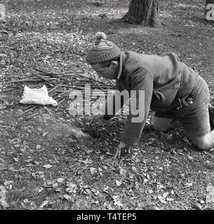 1960s, historical, a male adventure scout on his knees in a clearing in the forest getting the camp fire going, England, UK. - Stock Image