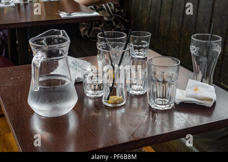 Empty drinking glasses and a jug of water on a table in a restaurant. - Stock Image