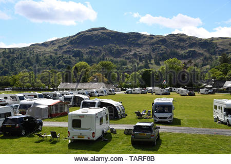 Dozens of caravans and campers parked up at Grasmere village in Cumbria in the Lake District for a camping holiday in the good sunny weather - Stock Image