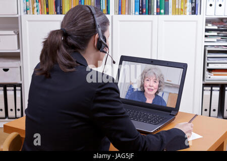 Female lawyer with headset in front of her laptop writing something on a paper while having a live video chat with - Stock Image