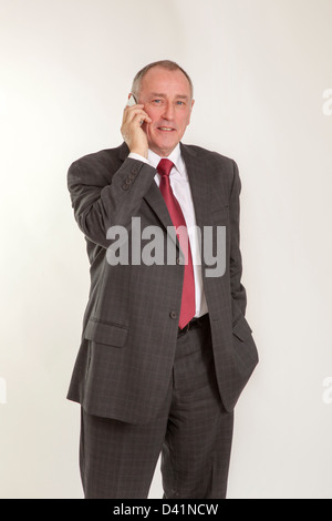Mature man in 50s wearing a grey suit, talking on a cellphone or mobile phone, looking to camera smiling. - Stock Image