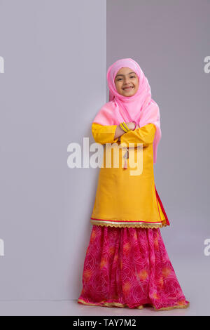 young Muslim girl with hijab folding hands and smiling - Stock Image