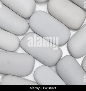 background of white smooth stones of elongated shape, top view - Stock Image
