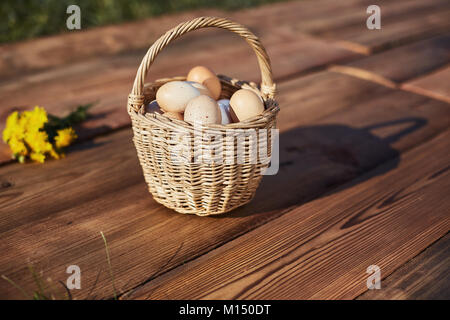 Fresh Chicken eggs in basket on rustic wooden background. Bouquet with yellow dandelions - Stock Image