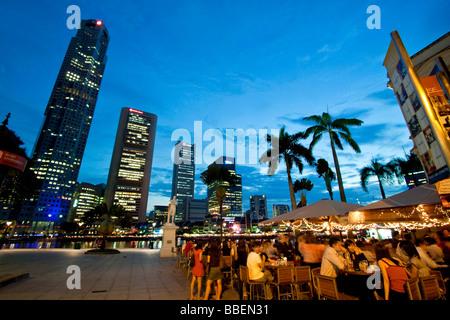 Skyline of Singapores Raffles Statue street cafe South East Asia twilight - Stock Image