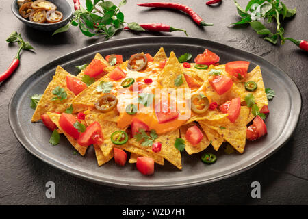 Mexican nachos with a cheese sauce, chili and jalapeno peppers, tomatoes, and cilantro leaves - Stock Image